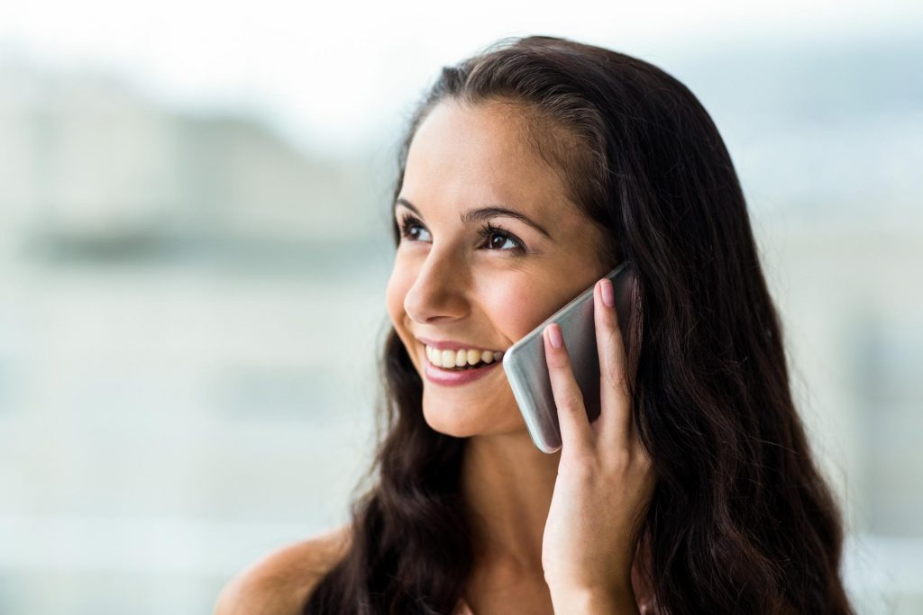 smiling woman taking phone call