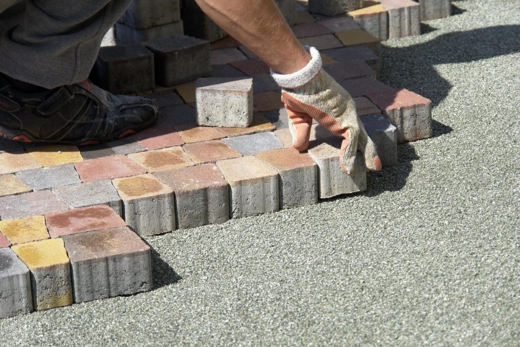 worker is putting stones together for patio